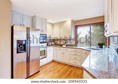 Elegant kitchen with white storage cabinets and granite tops - stock photo