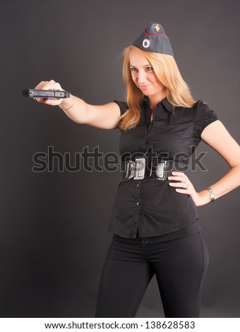elegant lady in black holding gun and aiming - stock photo