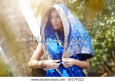 Elegant lady in blue Indian sari standing at the palm in wild jungle. Natural sunlight and colors - stock photo