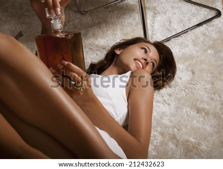 elegant lady in white dress with bottle. indoor shot - stock photo