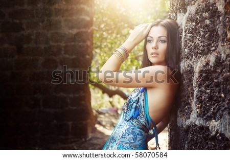 Elegant lady outdoors near the old stony walls. Sunlight at the background - stock photo