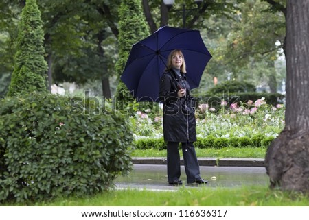 Elegant lady walking in a beautiful park under umbrella on a cold rainy day - stock photo