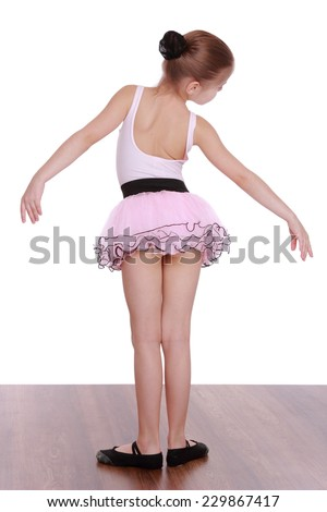 Elegant little ballerina in a pink tutu standing back to camera isolated on white - stock photo