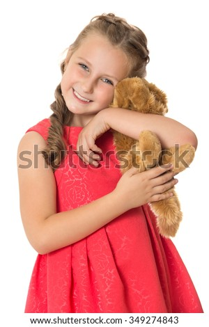 Elegant little girl in brightly red dress gently hugs the Teddy bear . Closeup - Isolated on white background - stock photo