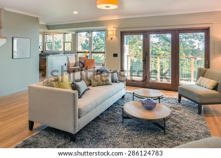 Elegant Living room with couch, french doors and view windows. Living room interior with copy space for art with hand-woven natural colored fine sisal rug open space living room within nature. - stock photo