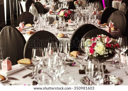 Elegant luxury cutlery and tablewear with flowers at hotel wedding reception - stock photo