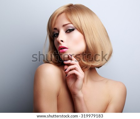 Elegant makeup blond woman with manicured nails posing on blue background - stock photo