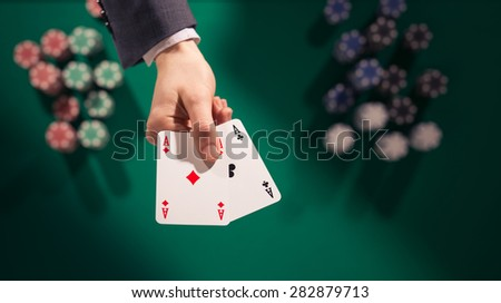 Elegant male poker player holding two aces with stacks of chips on background and green table, top view - stock photo