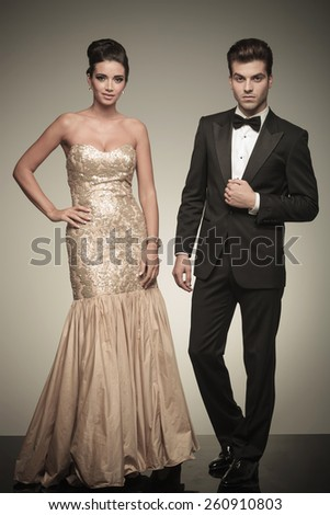 Elegant man and woman posing on grey studio background, she is holding her hand on her waist while he is fixing his jacket. - stock photo