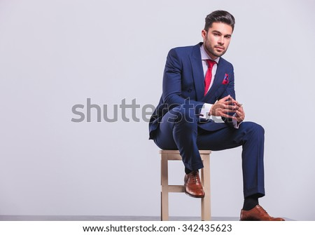 elegant man in business suit sitting in studio with palms touching while resting his leg on chair - stock photo