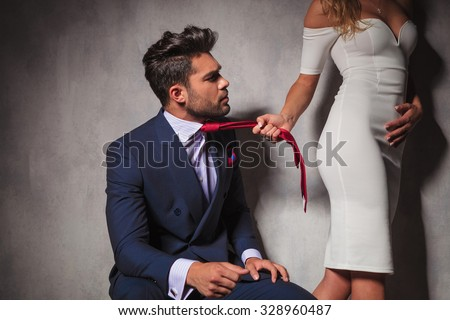 elegant man looking at his lover while she is pulling his tie and walks away in studio - stock photo