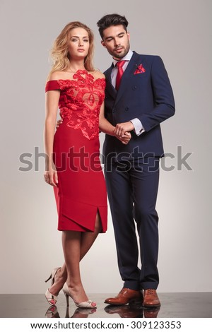 Elegant man looking down while holding his girlfriends hand. - stock photo