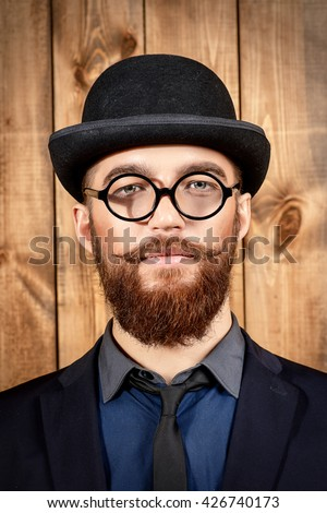 Elegant man wearing suit, bowler hat and spectacles. Old style fashion.  - stock photo
