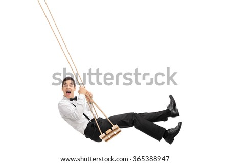 Elegant man with a black bow-tie and suspenders swinging on a wooden swing isolated on white background - stock photo