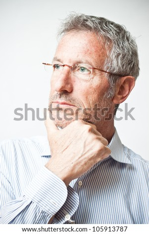 Elegant mature man portrait wearing a pair of glasses lost in thought - stock photo