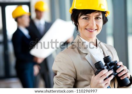 elegant middle aged female architect with binoculars - stock photo