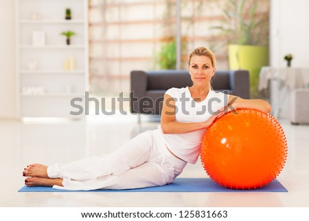 elegant middle aged sitting on mat with exercise ball - stock photo
