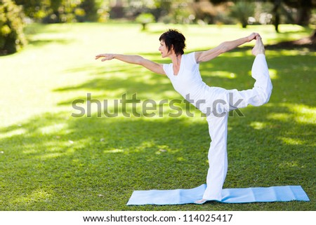 elegant middle aged woman doing yoga outdoors - stock photo