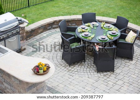 Elegant outdoor living space on a paved brick patio with a summer kitchen and barbecue and a table laid with formal place settings for dinner, high angle view - stock photo