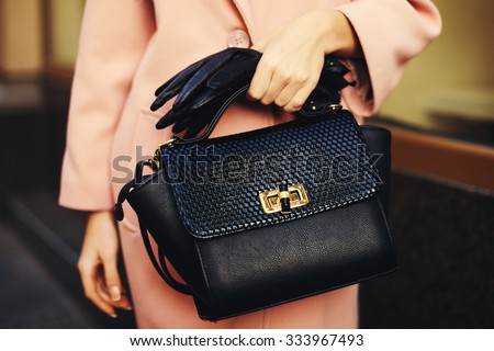 Elegant outfit. Closeup of black leather bag handbag in hand of stylish woman. Fashionable girl on the street. Female fashion. Toned - stock photo