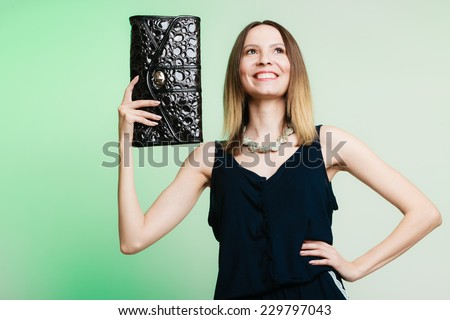 Elegant outfit. Young stylish woman fashionable girl holding black handbag on green. Fashion and female beauty. Studio shot. - stock photo