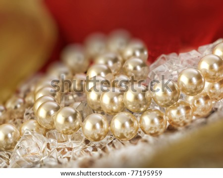 Elegant pearls over ice with ribbon very shallow depth of field - stock photo