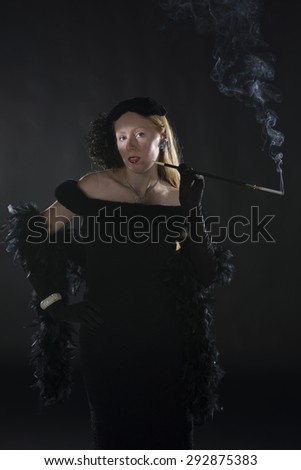 Elegant Portrait of Glamorous Woman Smoking Cigarette and Dressed in Vintage Clothing, Three Quarter Length Portrait in 1940s Film Noir Style - stock photo