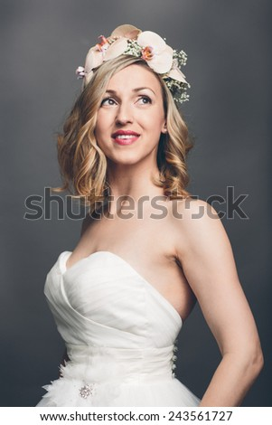 Elegant pretty bride with flowers in her hair wearing a strapless white bridal dress standing looking meditatively up into the air with a tender smile, upper body over grey - stock photo