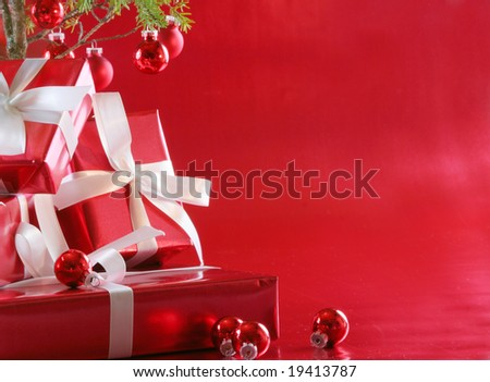 Elegant red presents under Christmas tree with deep rich red background. - stock photo