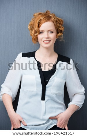 Elegant relaxed beautiful young redhead woman standing against a grey background with her hands in her pockets giving the camera a charming smile - stock photo