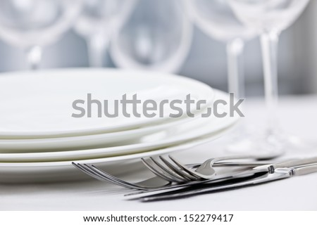 Elegant restaurant table setting for fine dining with plates cutlery and stemware - stock photo
