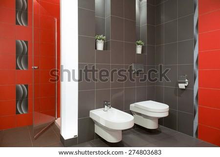 Elegant restroom with ceramic toilet and bidet - stock photo