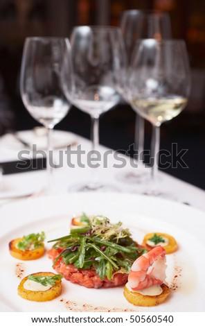 Elegant salmon tartare on restaurant table - stock photo