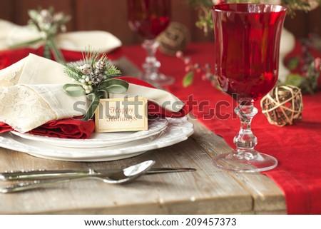 Elegant selective focus Christmas dining scene on rustic wood table - stock photo