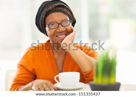elegant senior african woman having tea at home - stock photo