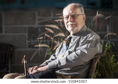 elegant senior gentleman sit on a chair at a wedding ceremony,  holding a walking stick  - stock photo