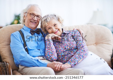 Elegant seniors in smart clothes sitting on sofa and looking at camera - stock photo