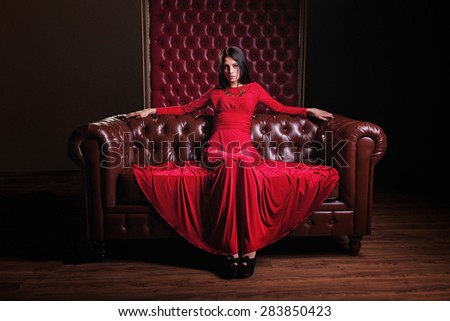 elegant sensual young brunette woman in red dress sitting on leather sofa and looking at camera - stock photo