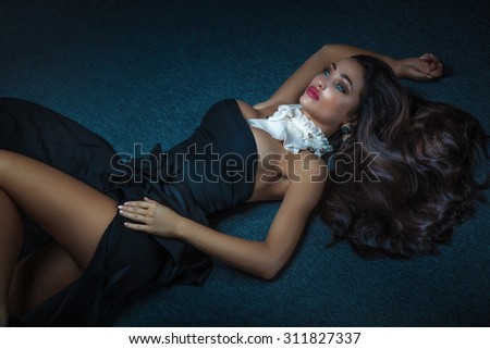 Elegant sexy brunette woman lying on the floor in black fashionable dress. Girl with ceremonial makeup.  - stock photo