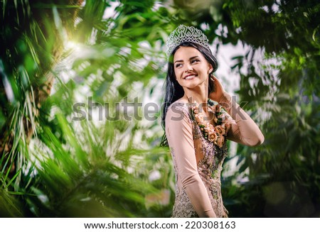 Elegant smiling lady with tiara on a head posing in a forest - stock photo