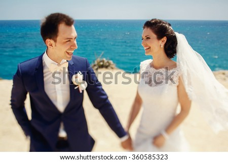 Elegant smiling young bride and groom walking on the beach, kissing and having fun, wedding ceremony near the rocks and ocean - stock photo