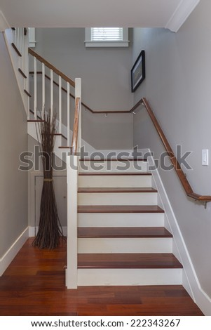 Elegant stairway with wooden railing and cheery wood floors.  - stock photo