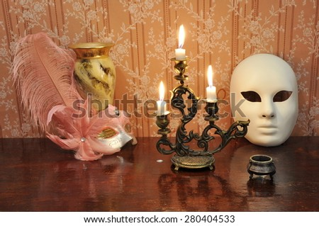 Elegant still life with  bronze candelabra, antique goblet and two masks on an old wallpaper background - stock photo
