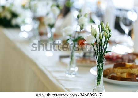 Elegant stylish decorated wedding reception tables with glasses and flowers in vase closeup - stock photo