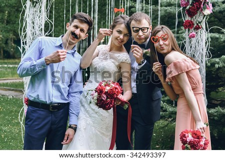 elegant stylish happy guests and bride and groom having funny photos on the background of arch - stock photo