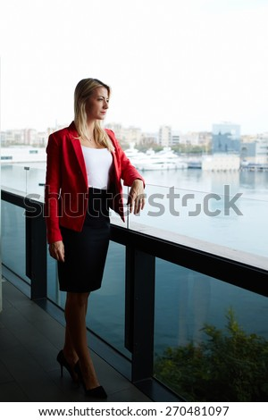 Elegant successful woman standing on the balcony of modern office building pensive looking away, rich well dressed woman standing in office exterior part with marina port view on background - stock photo
