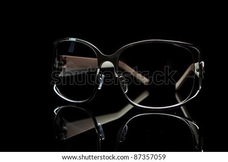 Elegant sunglasses on black background - stock photo