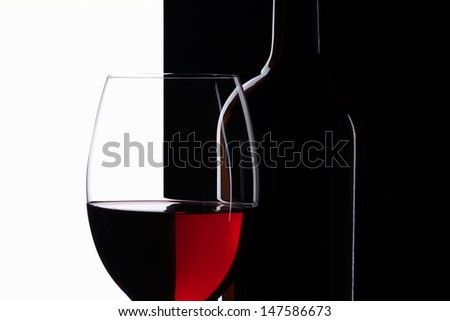 Elegant symmetry red wine glass and a wine bottle in black and white background - stock photo