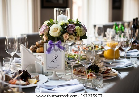Elegant table arrangement and catering at wedding reception, stylish bouquet centerpiece - stock photo