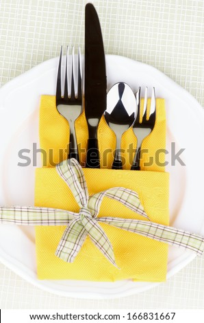 Elegant Table Setting with Fork, Table Knife, Spoon and Dessert Fork into Yellow Napkin Decorated with Green Checkered Bow on White Plate - stock photo